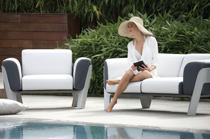 Ce fauteuil élégant de la marque Ego Paris est remarquable par la générosité de ses coussins.