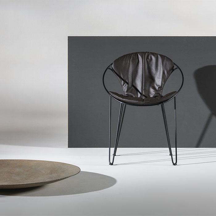 Chaise design de JOLI peut être recouverte d'un coussin en tissu ou cuir.